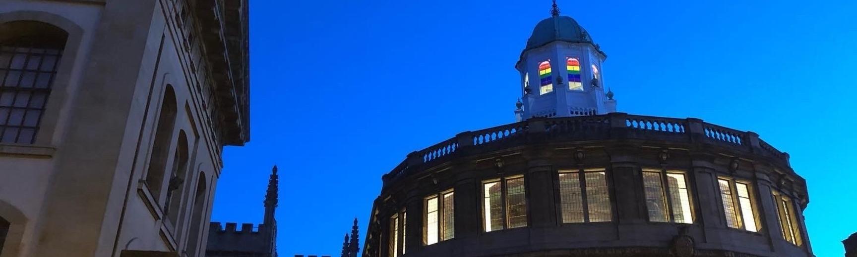 Photo of Sheldonian Theatre lit up against dark blue sky