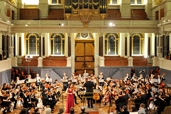 Photo of full orchestra with violin soloist performing a concert in the Sheldonian Theatre